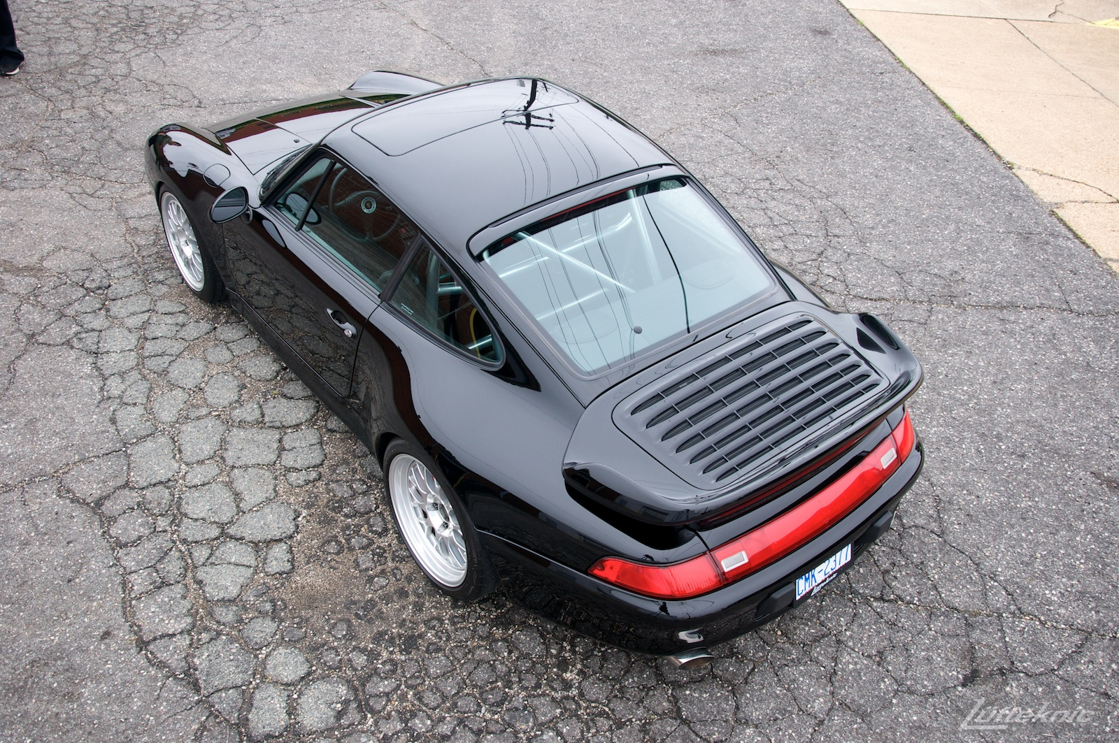 A view from above and behind a shiny black 993 Porsche Turbo in a parking lot.