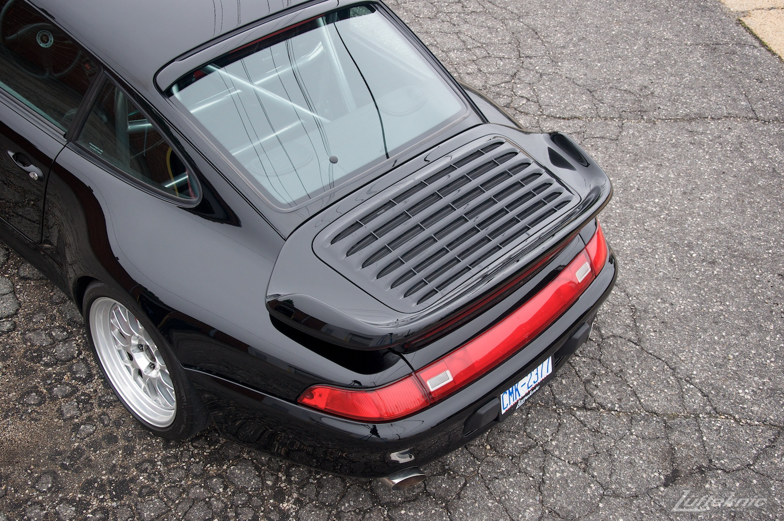 A view from above and behind a shiny black 993 Porsche Turbo in a parking lot showing rear lights and spoiler.