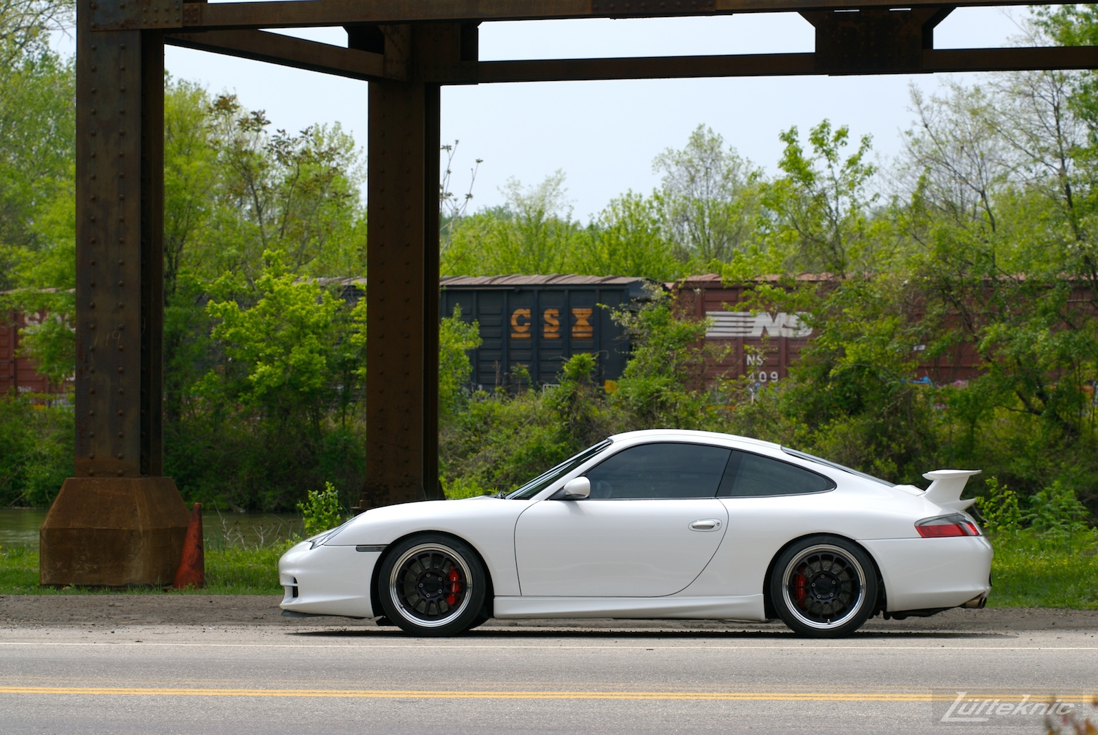A track-prepped white Porsche 996 Gt3 with Fikse wheels in front of a train.