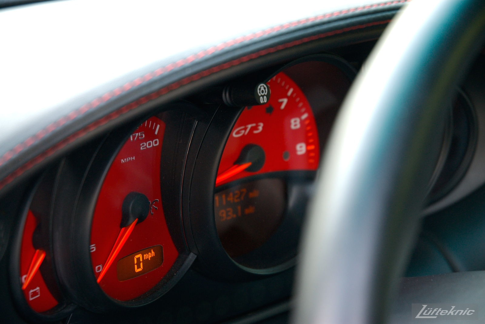 A track-prepped white Porsche 996 Gt3 with red gauges