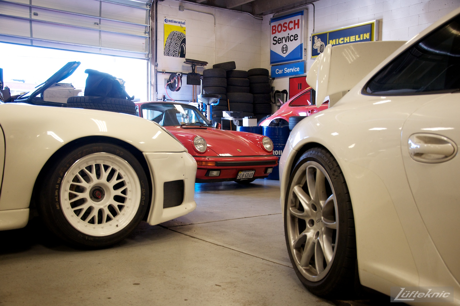 Two white Porsches and one red Porsche inside the Lufteknic shop.