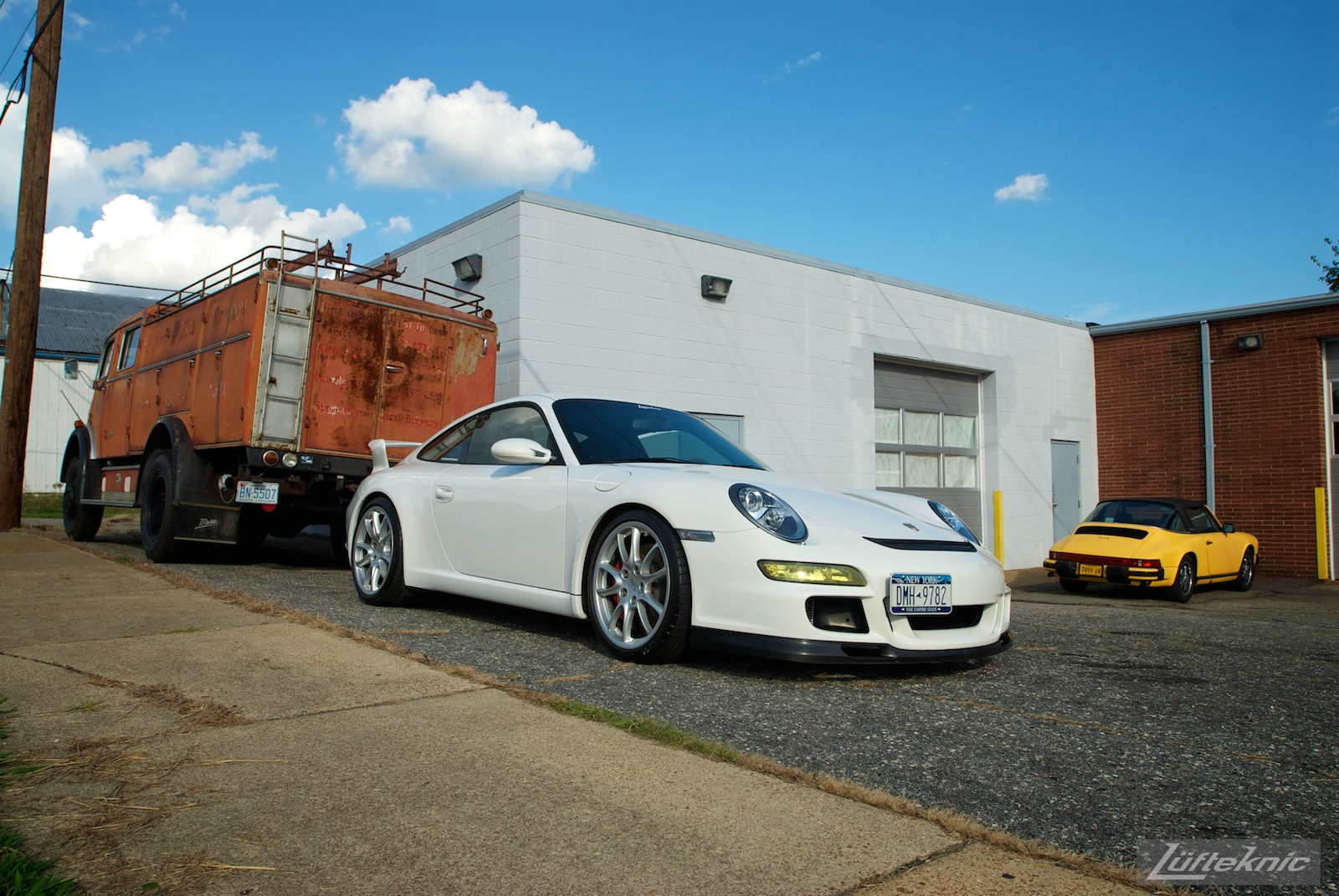 A white Porsche Gt3 poses with the Lufteknic fire truck in the parking lot, with an old yellow 911 Targa in the background.