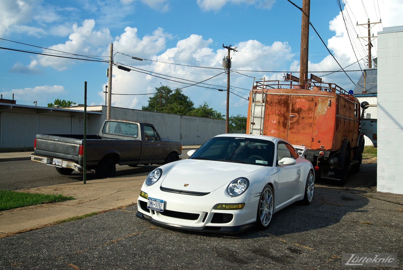 A white Porsche Gt3 poses with the Lufteknic fire truck in the parking lot, with an Ford in the background.