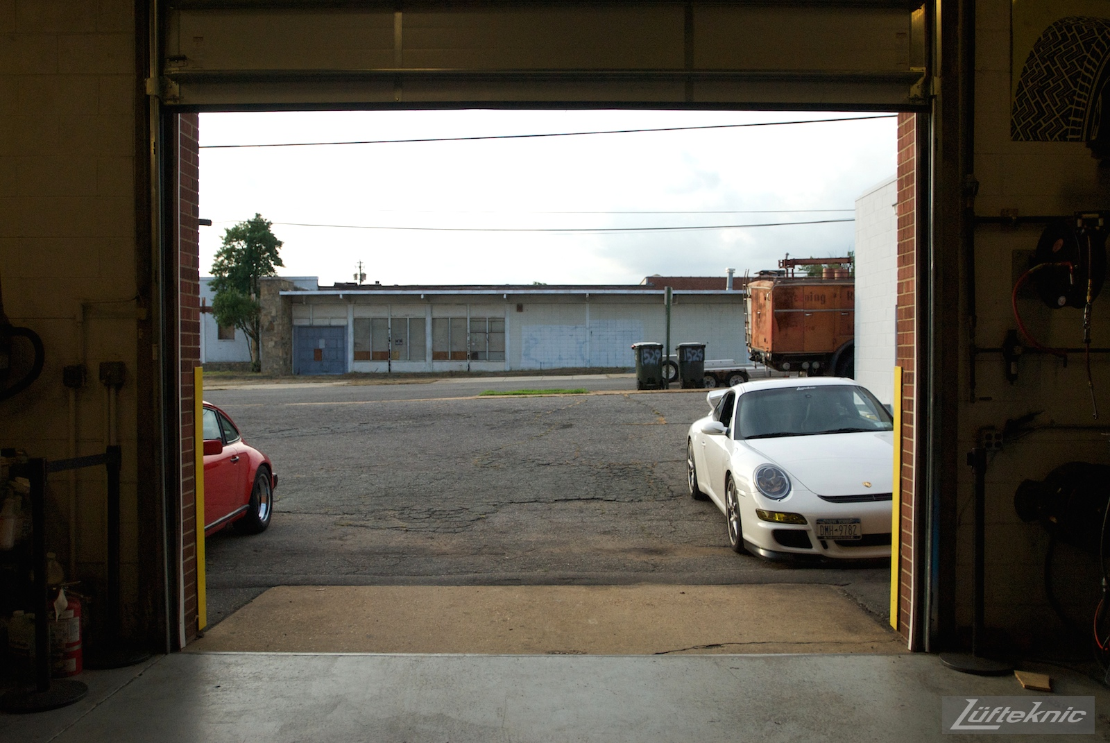A white 997 GT3 sitting just outside the Lufteknic shop door with other Porsches shown.