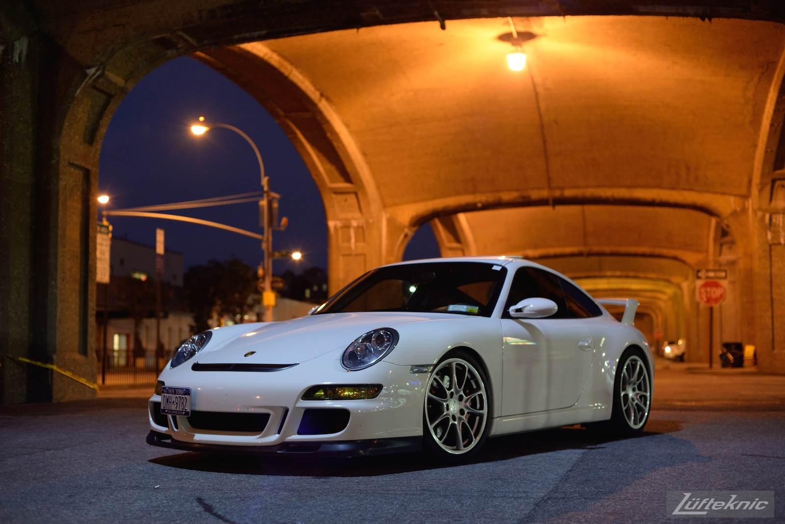 A white 997 GT3 viewed from the front under the 7 train bridge on Queens blvd at night.