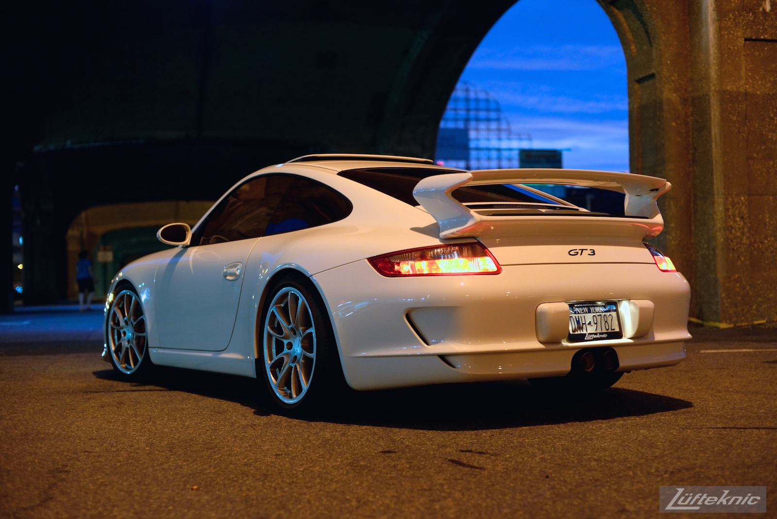 A white 997 GT3 viewed from behind under the 7 train bridge on Queens blvd at night.