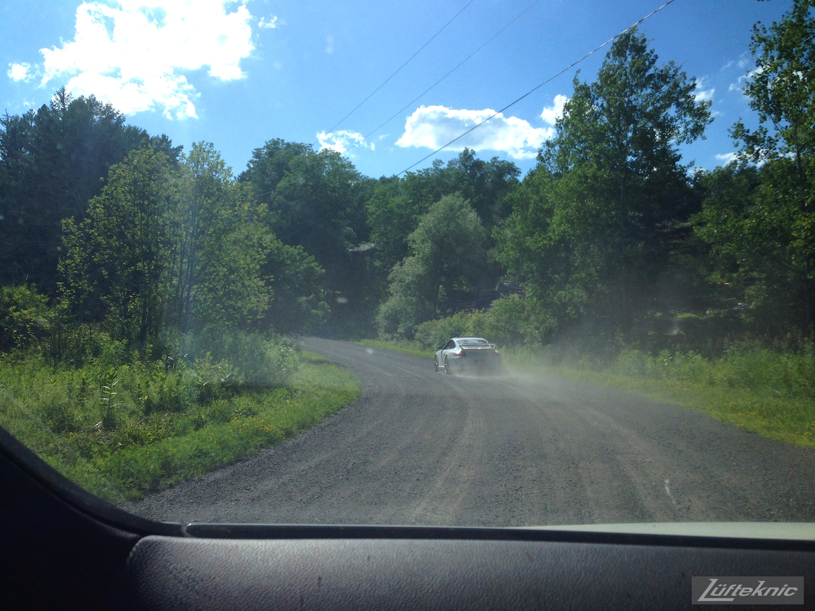 A white 997 GT3 driving on a gravel road.