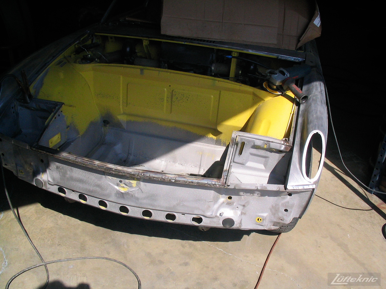 Front chassis pan repair on a yellow Porsche 914 being repaired.