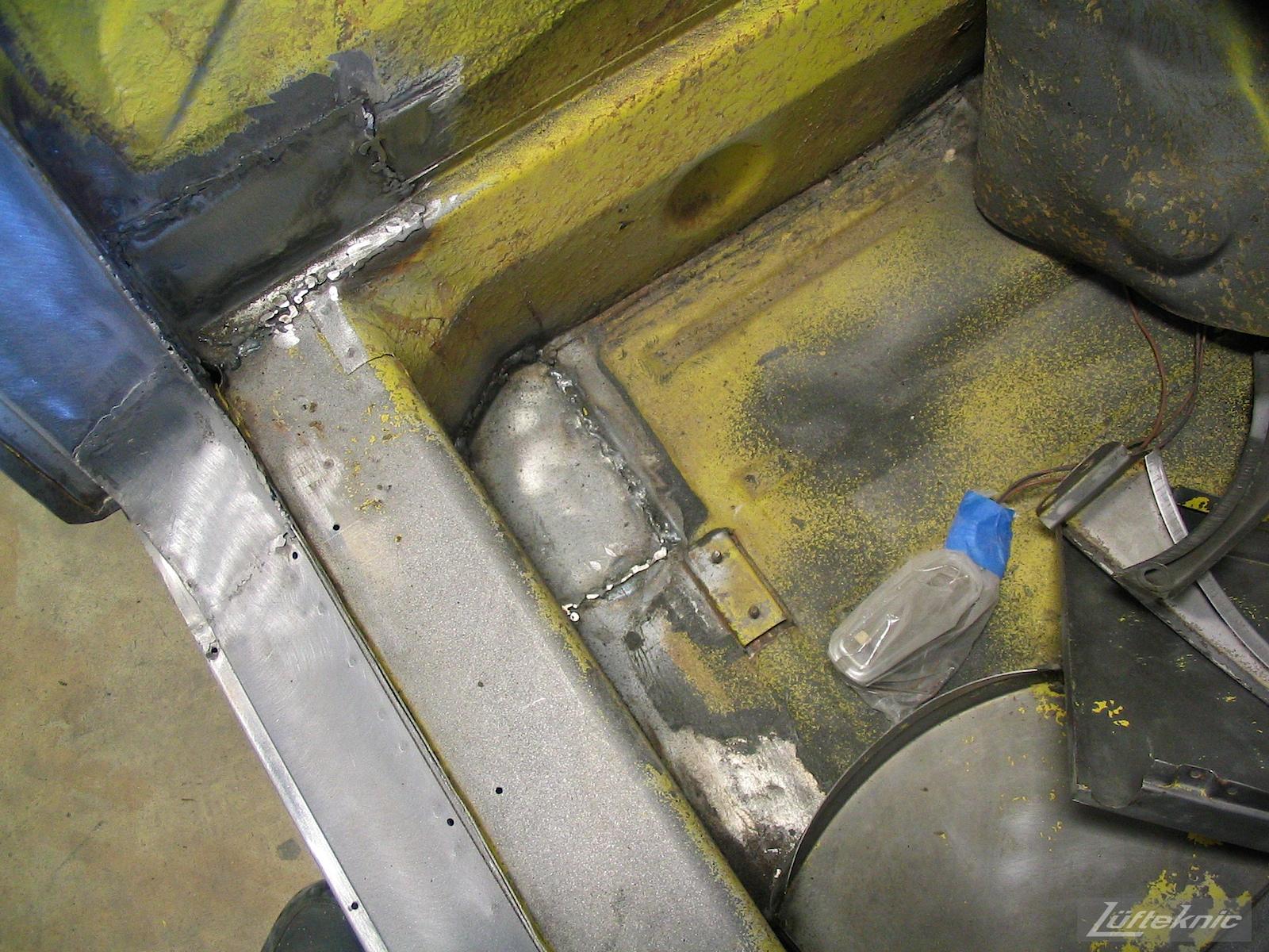 Rust repair close up on a yellow Porsche 914 being restored.