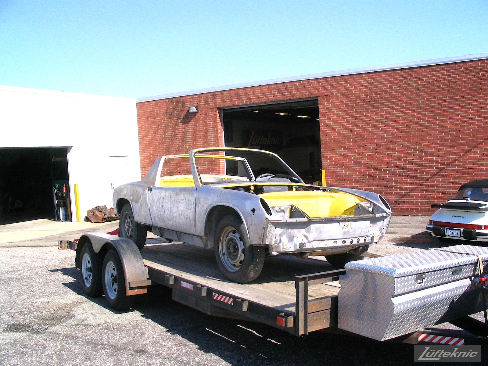 A stripped down yellow Porsche 914 shown mid-restoration on a trailer in the parking lot of Lufteknic.