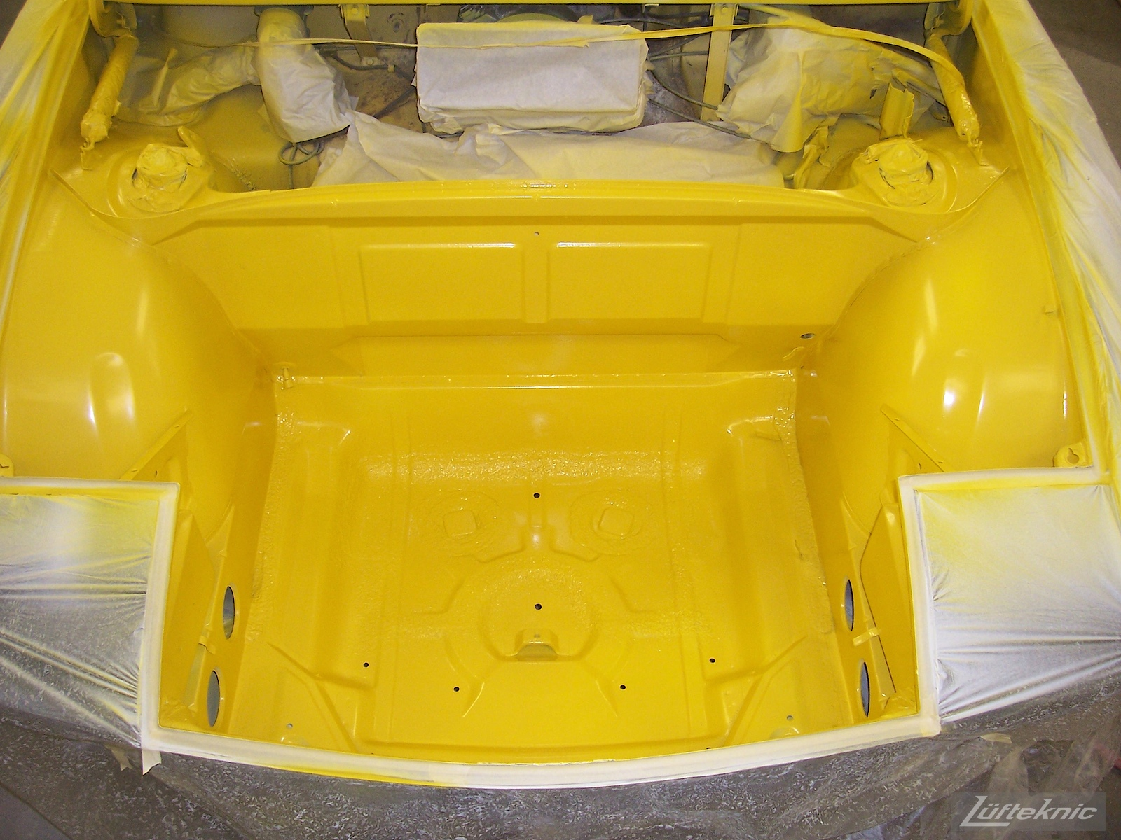 Fresh yellow paint in the front trunk of a Porsche 914 being restored.