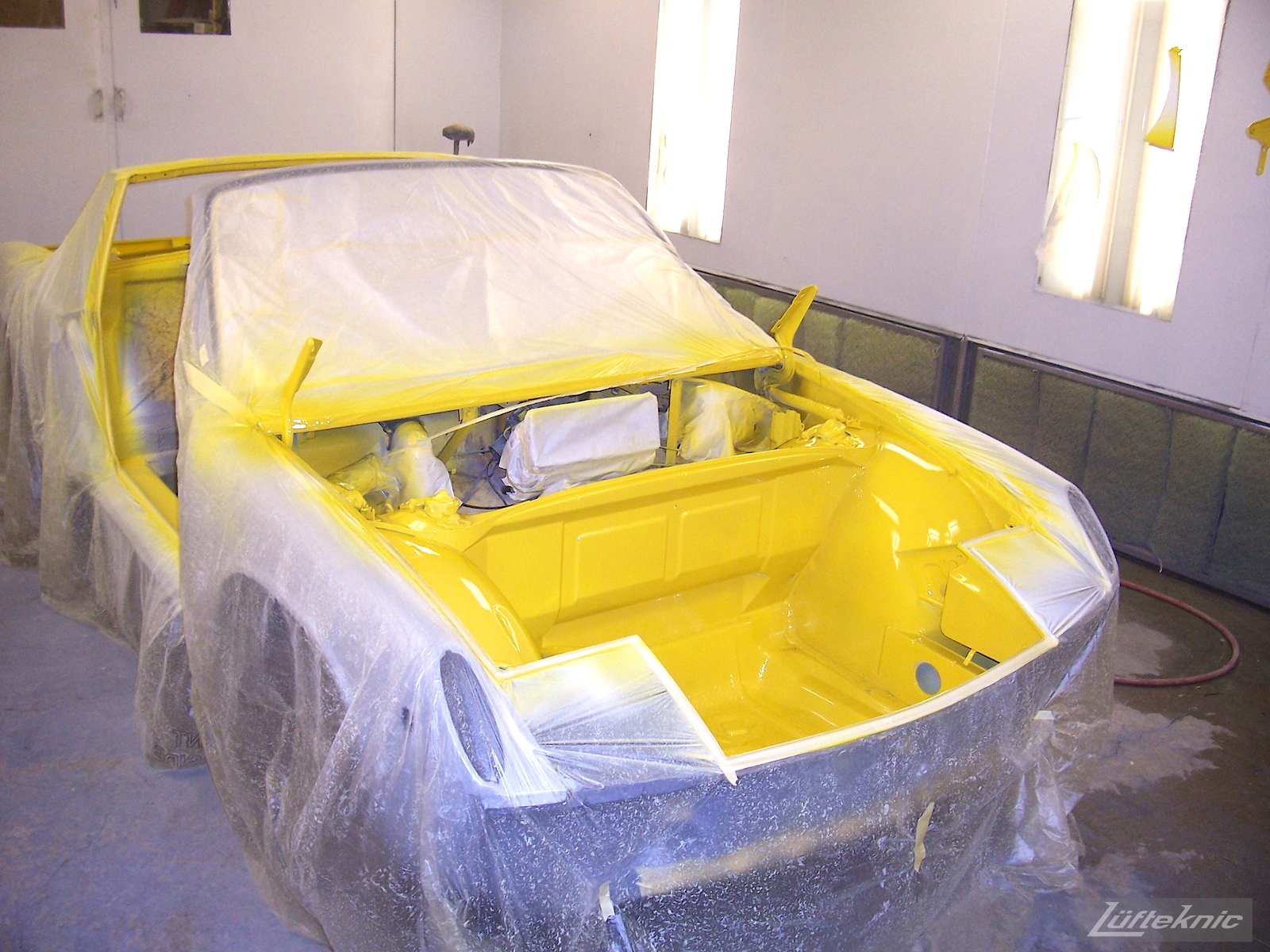 Fresh yellow paint on the interior pieces of a Porsche 914 being restored.