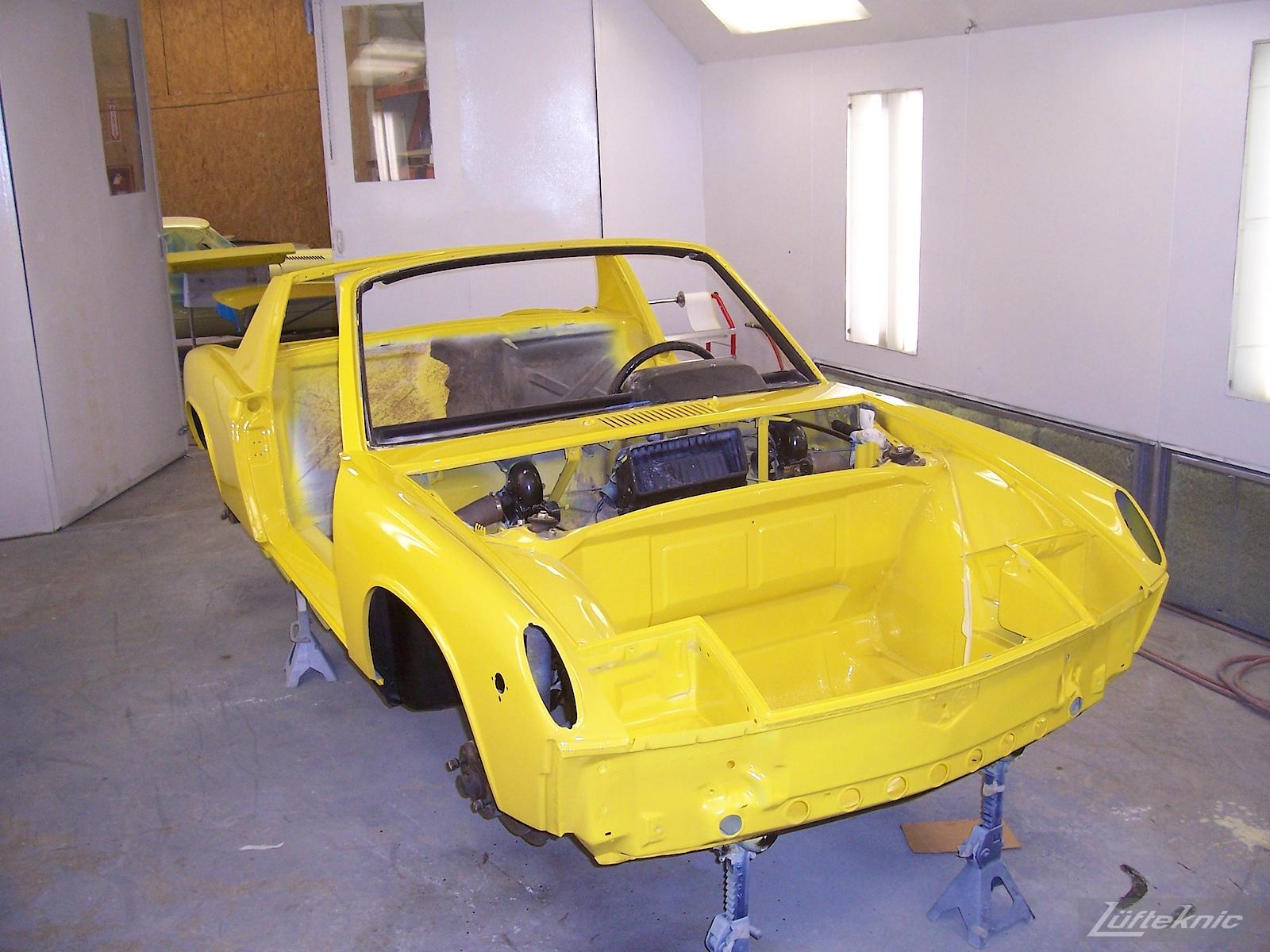 Fresh yellow paint on a Porsche 914 being restored.