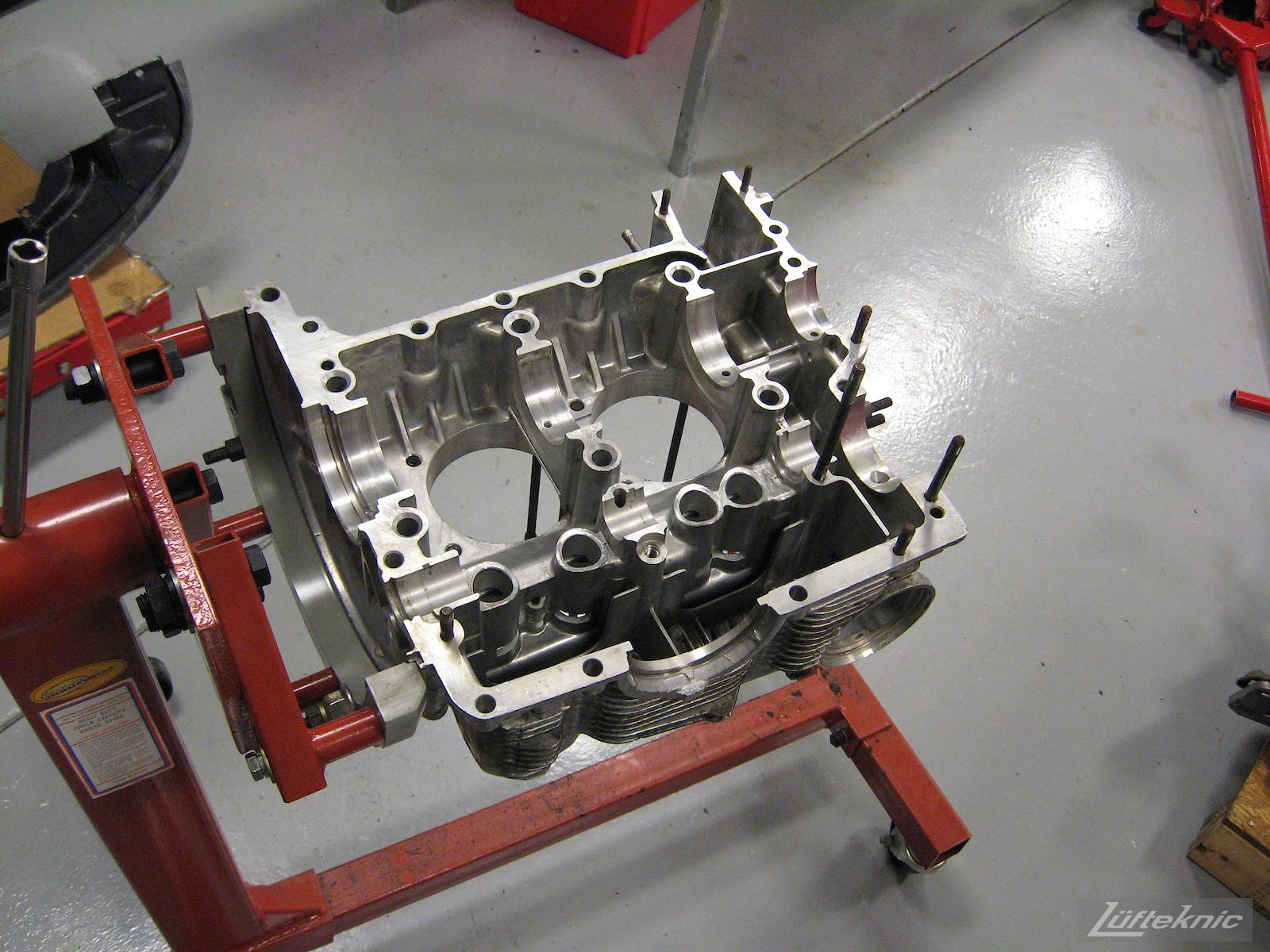 Stripped down Porsche engine case on a stand.