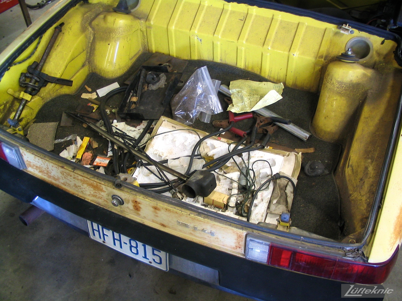 Various debris in the trunk of a yellow 914 before restoration.