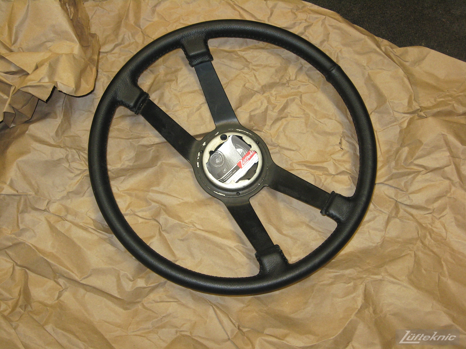 Refinished steering wheel for a 914 sitting on packing paper.
