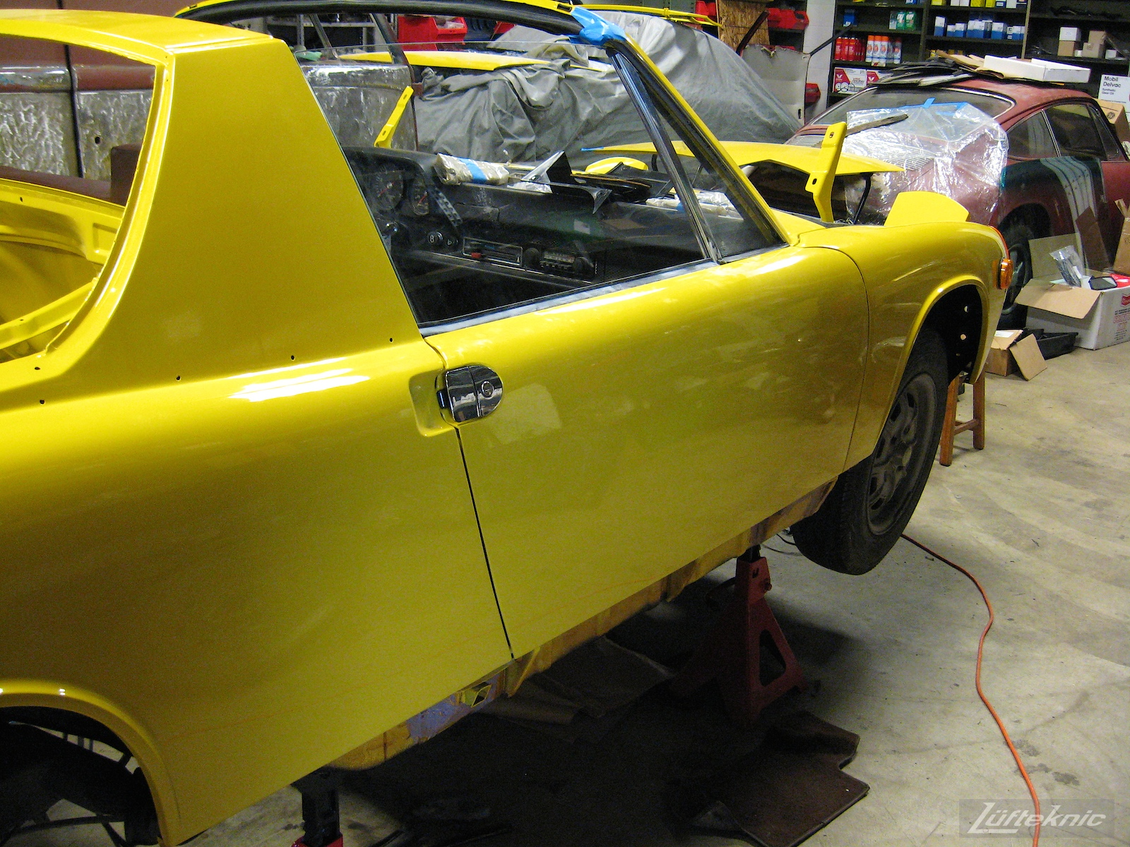 Reassembling a restored yellow Porsche 914 at Lufteknic.