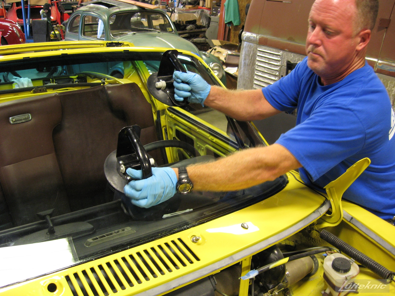 Installing the windshield into a restored yellow Porsche 914 at Lufteknic.