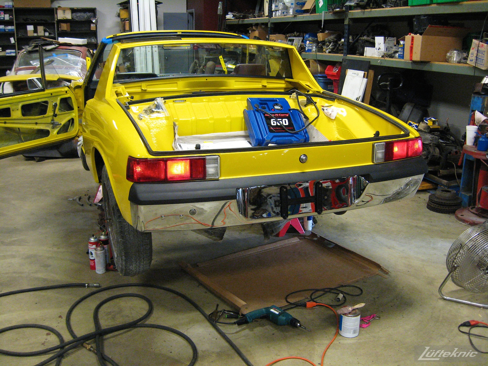 Illuminated rear tail lights on a restored yellow Porsche 914 at Lufteknic.