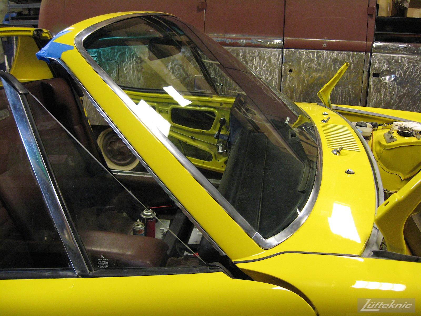 Installed windshield details on a restored yellow Porsche 914 at Lufteknic.