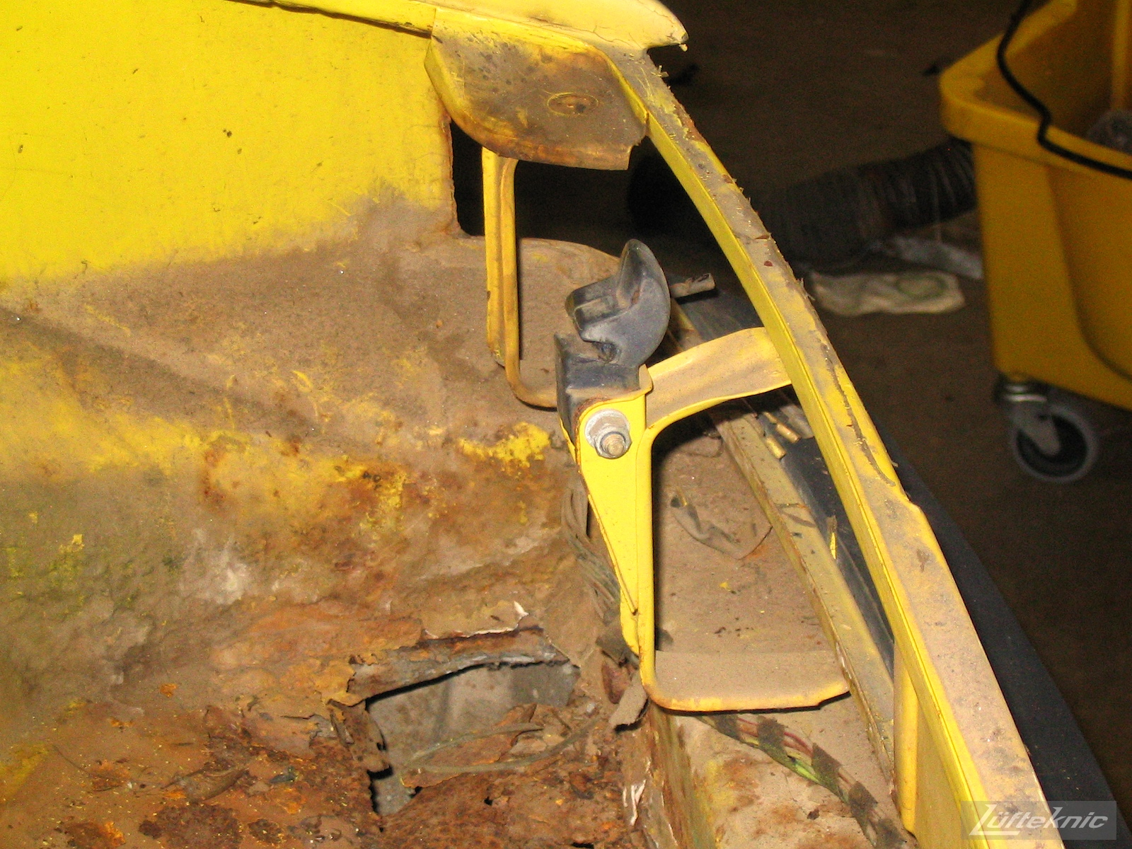 Significant rust damage on the chassis of a yellow Porsche 914.
