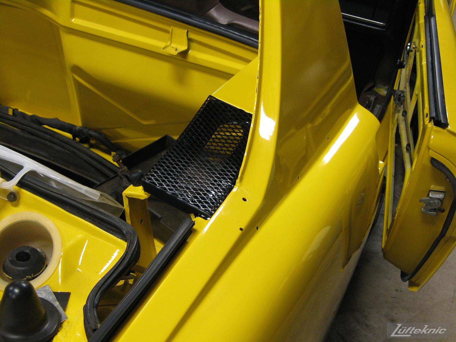 Rear engine decklid cover details on a restored yellow Porsche 914 at Lufteknic.