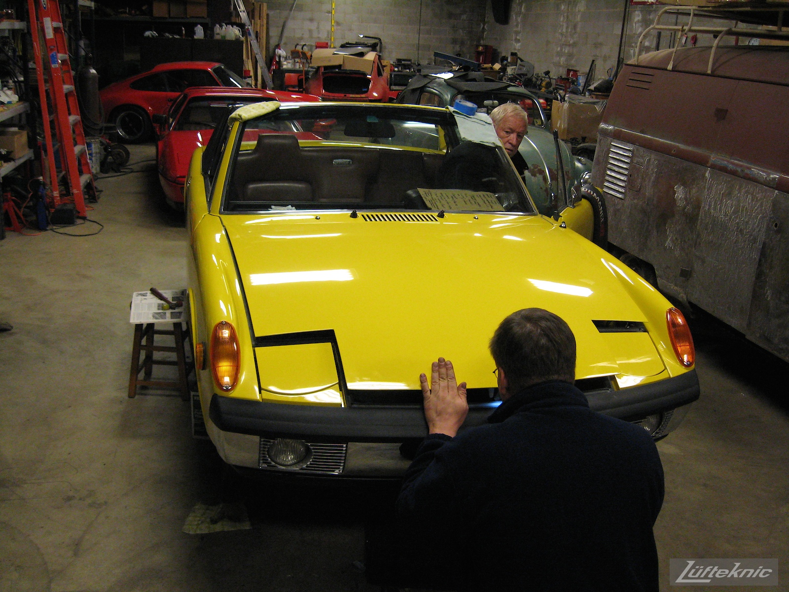 Checking hood clearance on a restored yellow Porsche 914 at Lufteknic.