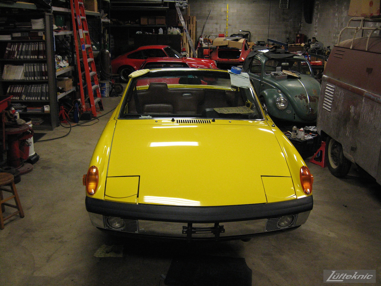 nearly done, hood installed while other projects sit around a restored yellow Porsche 914 at Lufteknic.