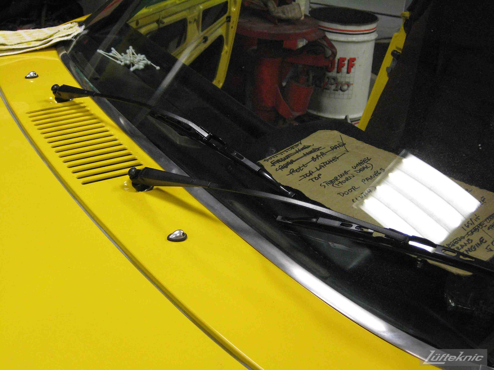 Windshield wiper details with a checklist on the dash of a restored yellow Porsche 914 at Lufteknic.