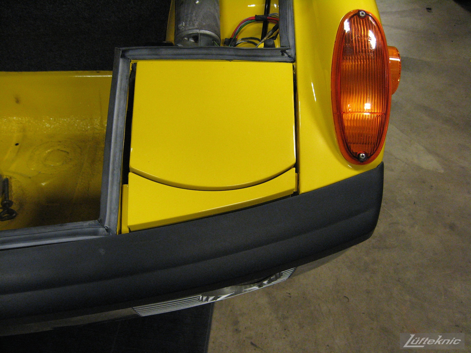Front bumper and lighting details on a restored yellow Porsche 914 at Lufteknic.
