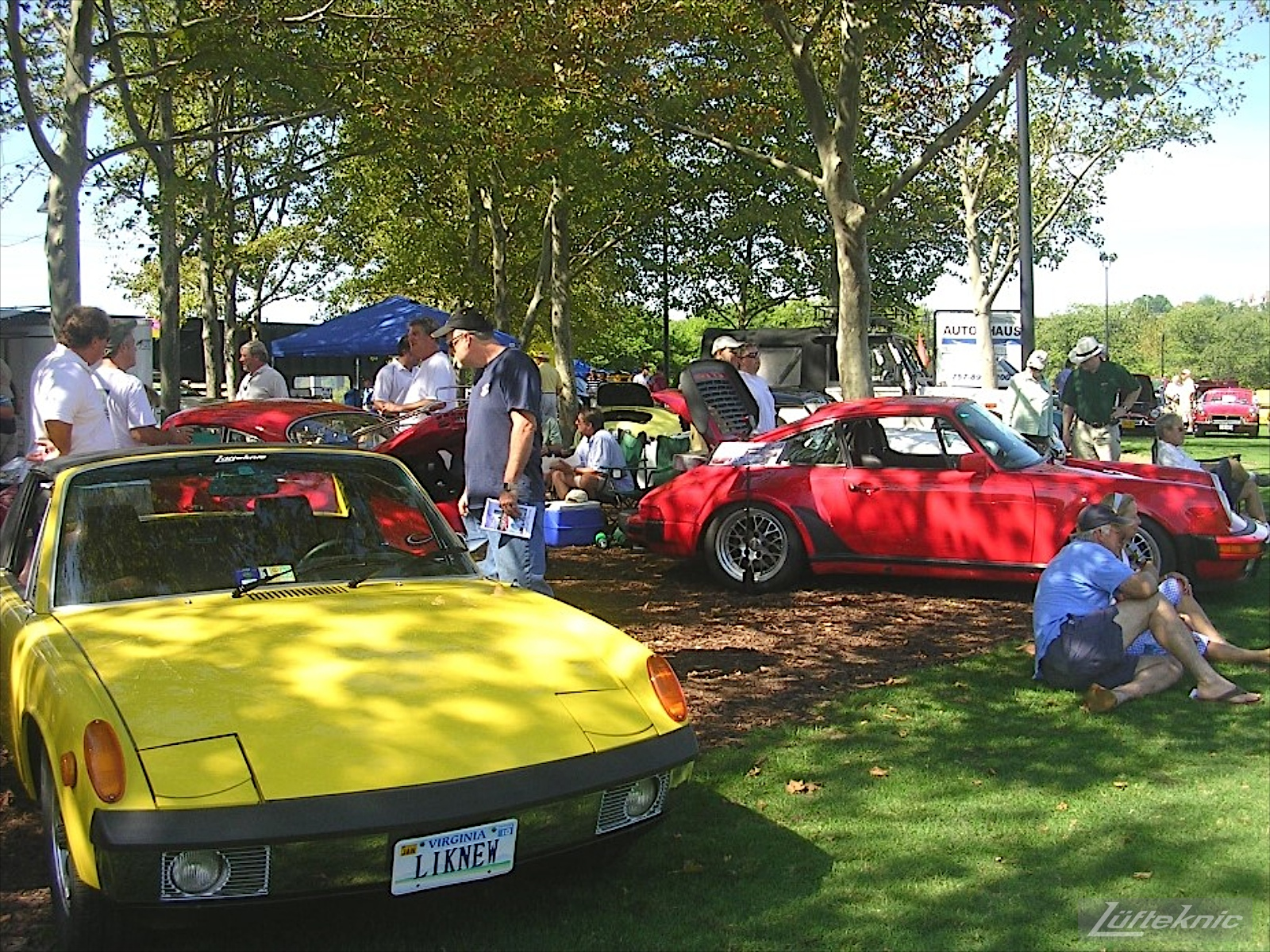 A restored yellow Porsche 914 on display with other Porsches at a car show.