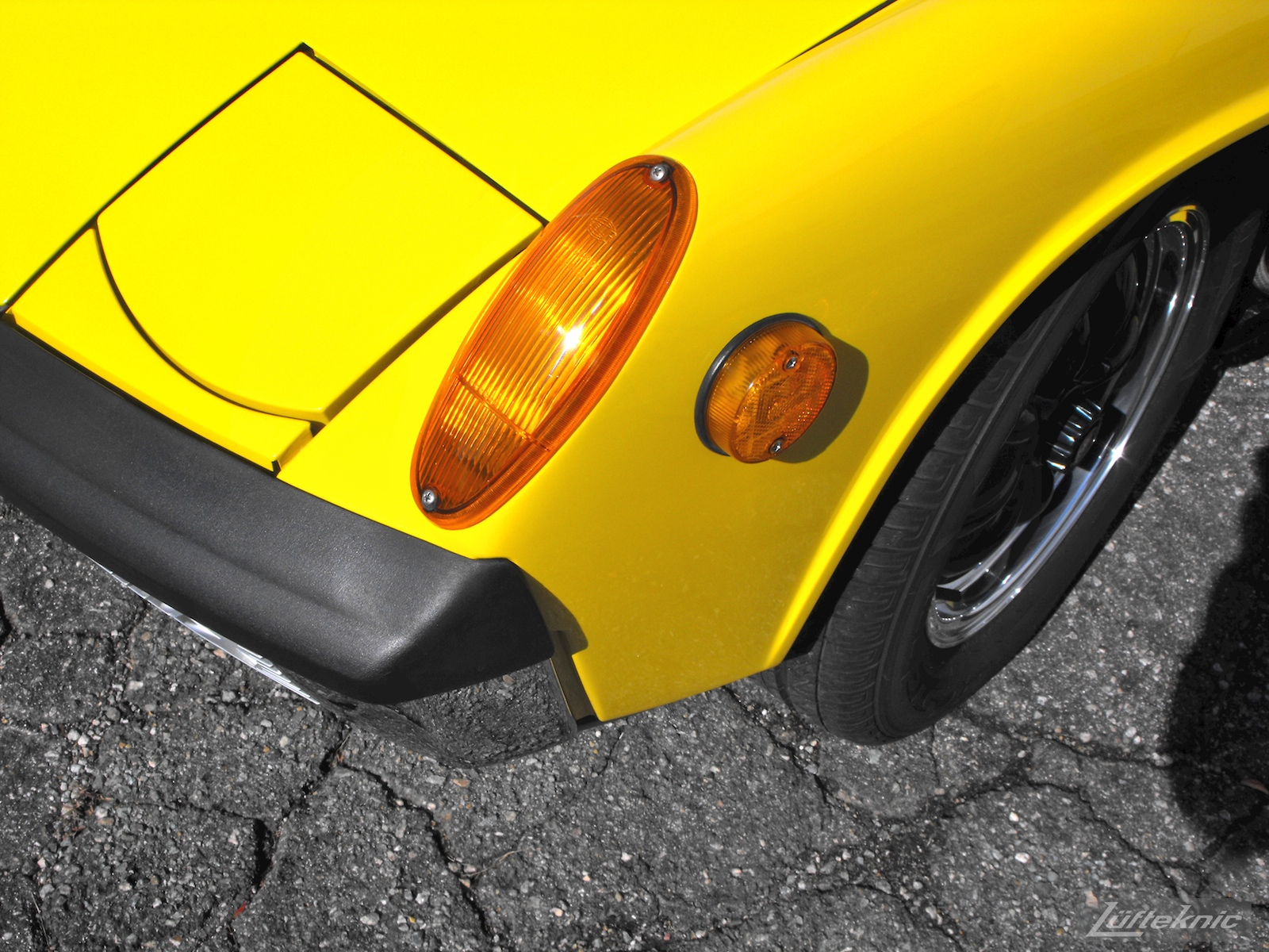 A completely restored yellow Porsche 914 posing in the parking lot of Lufteknic.