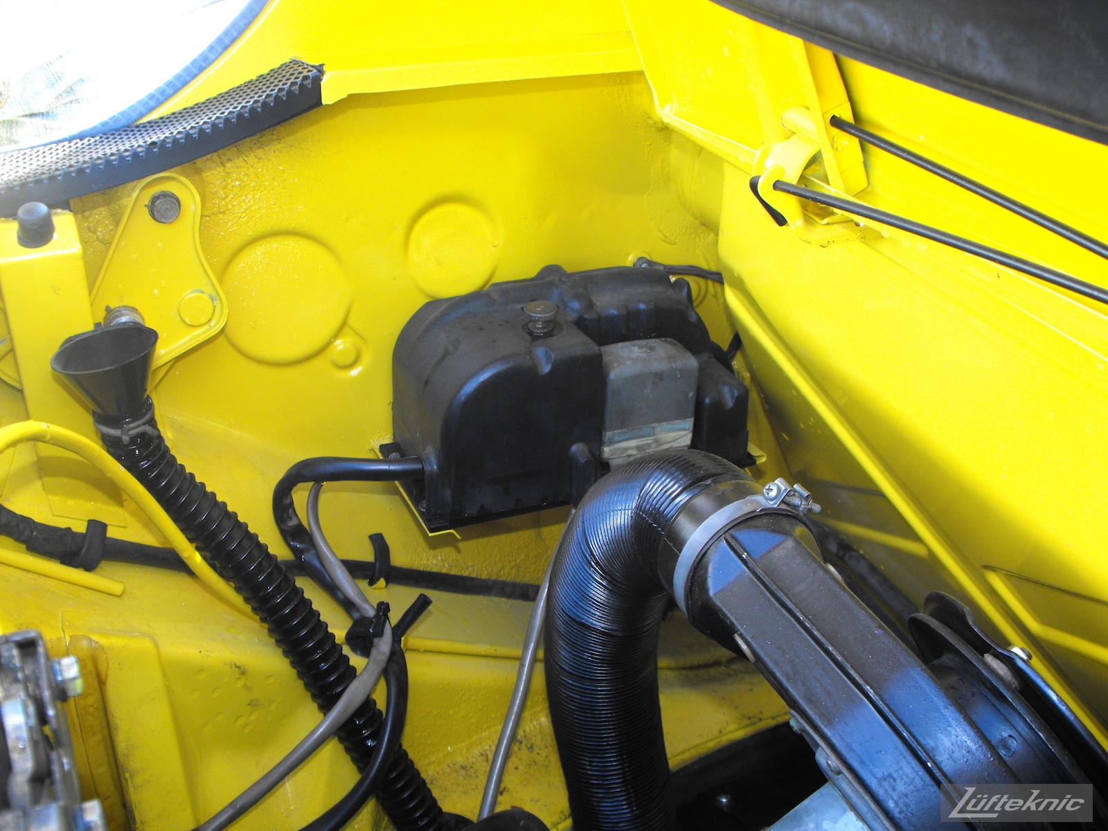 Engine details on a completely restored yellow Porsche 914 posing in the parking lot of Lufteknic.