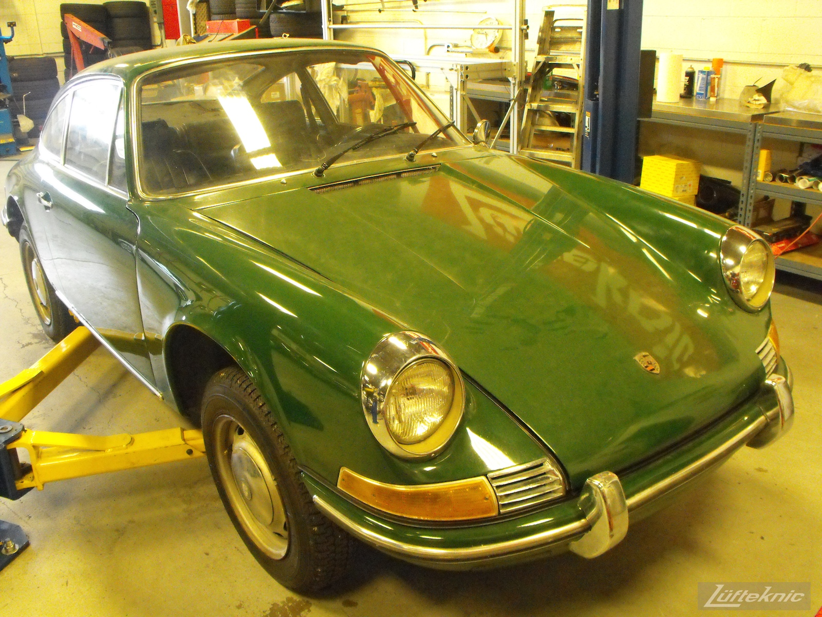 An Irish Green Porsche 912 undergoing restoration at Lufteknic with the car on a lift, showing original paint and trim.