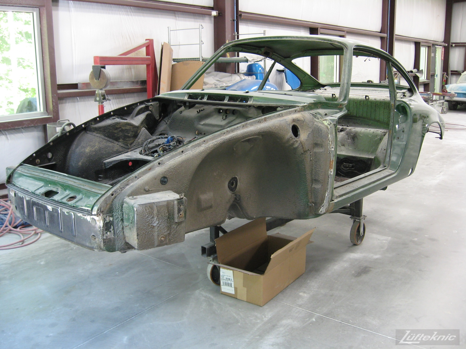 Body shell on a rack ready for sanding and refinishing of an Irish Green Porsche 912 undergoing restoration at Lufteknic.