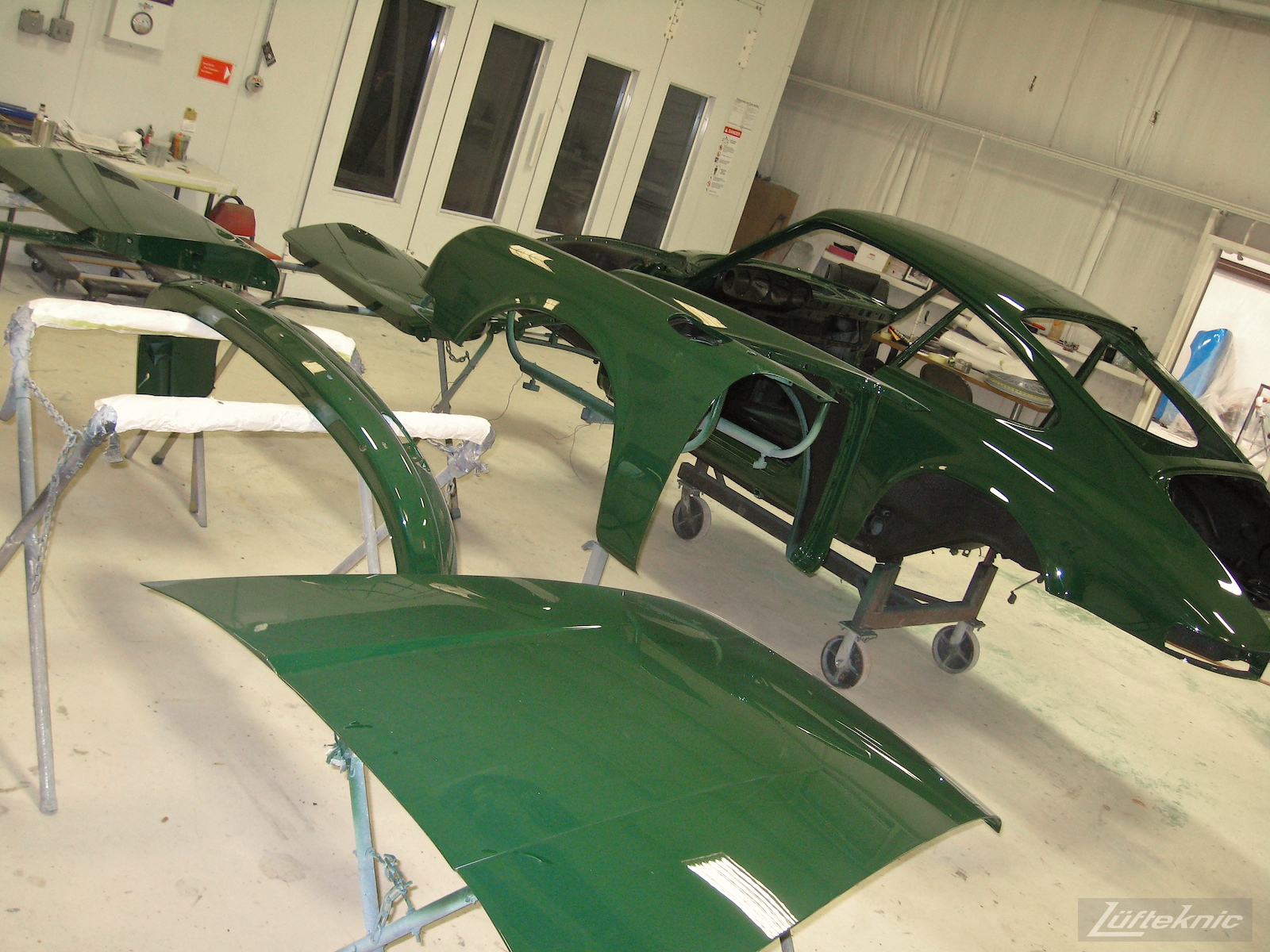Freshly painted body panels and shell of an Irish Green Porsche 912 undergoing restoration at Lufteknic.