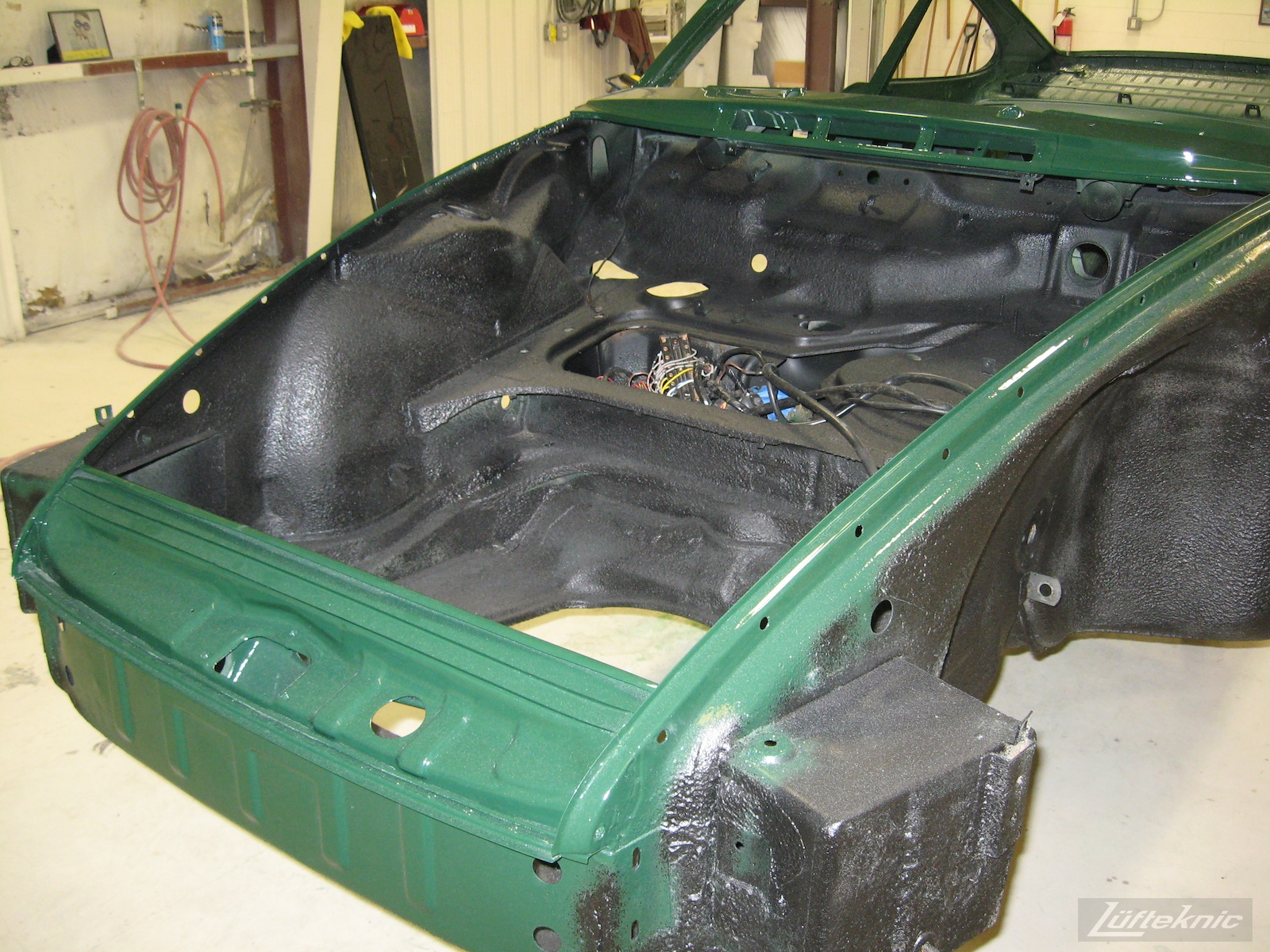 Freshly painted and coated body shell front pan detail of an Irish Green Porsche 912 undergoing restoration at Lufteknic.