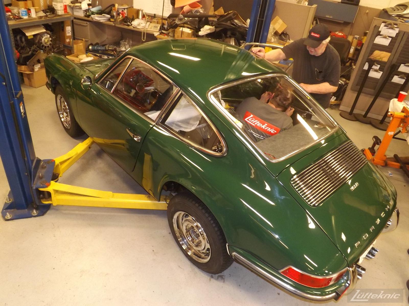 Installing windows into an Irish Green Porsche 912 undergoing restoration at Lufteknic.