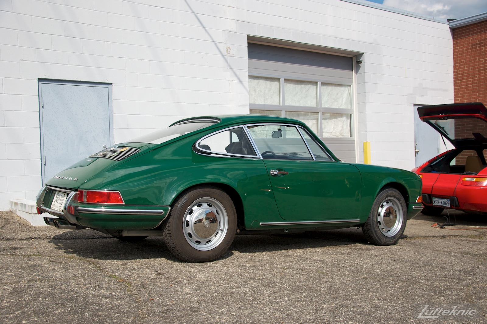 An Irish Green Porsche 912 which has been completely restored by Lufteknic sitting in the shop parking lot.