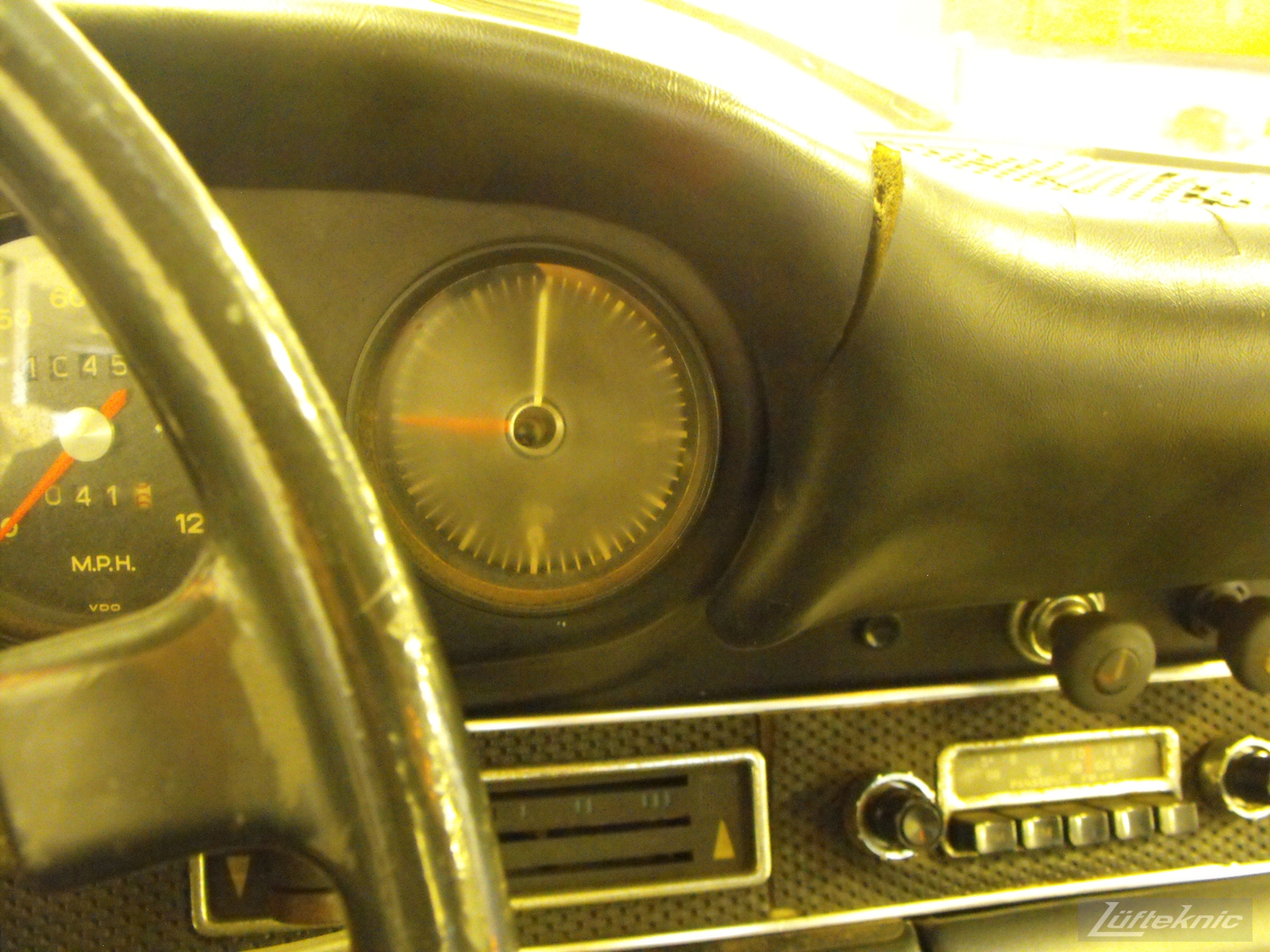 A close up of an aged clock and cracked dash of an Irish Green Porsche 912 undergoing restoration at Lufteknic.