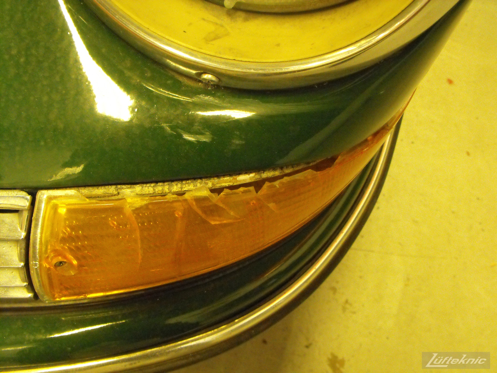 A cracked front turn signal lens of an Irish Green Porsche 912 undergoing restoration at Lufteknic.
