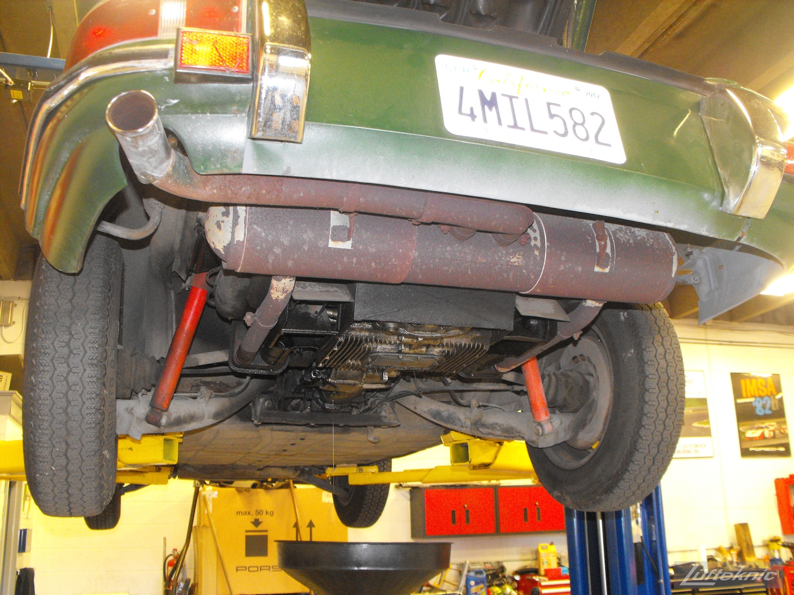 A rusty muffler exposed and oily bottom of the engine of an Irish Green Porsche 912 undergoing restoration at Lufteknic.