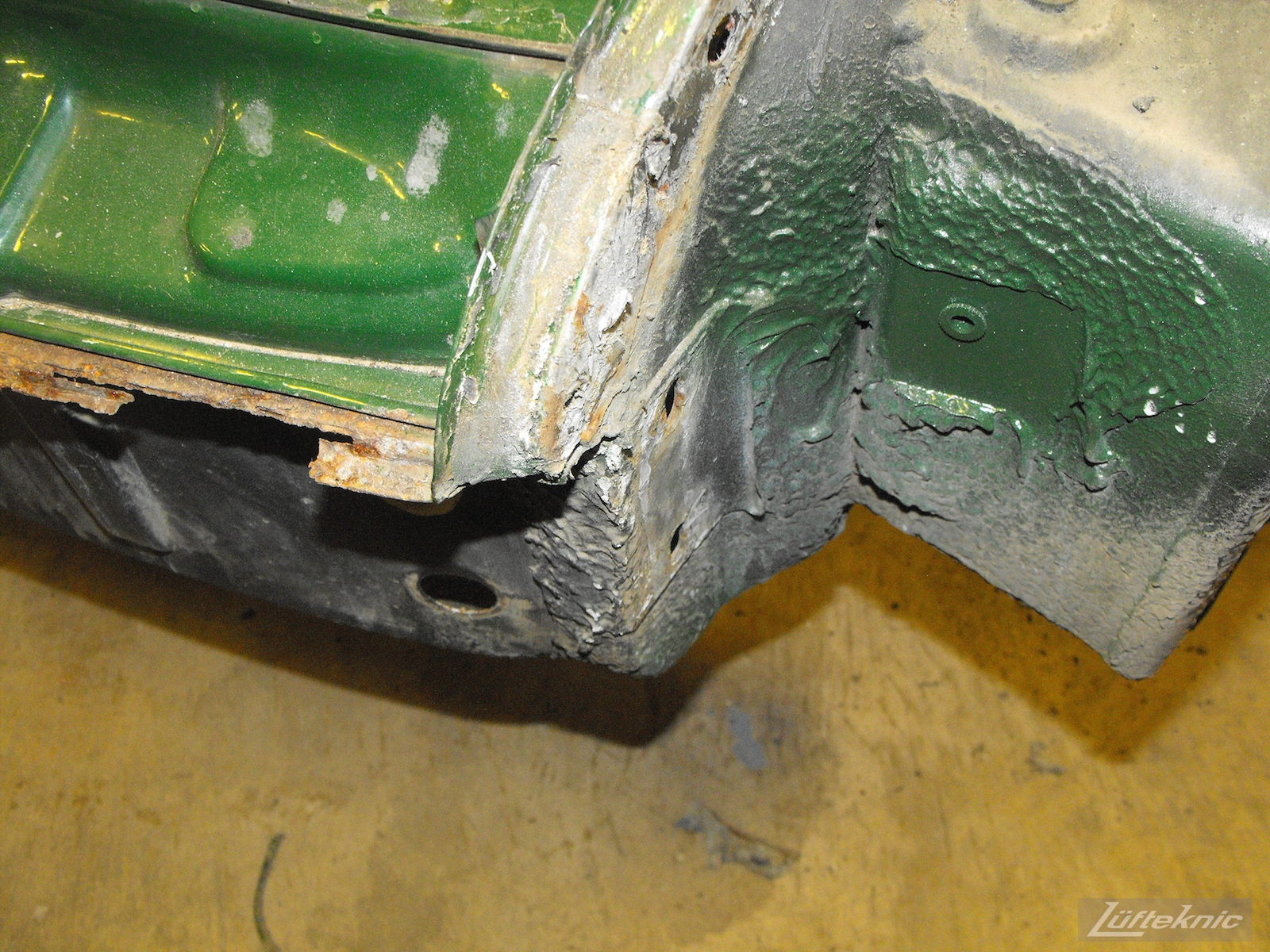 Front pan damage on an Irish Green Porsche 912 undergoing restoration at Lufteknic.