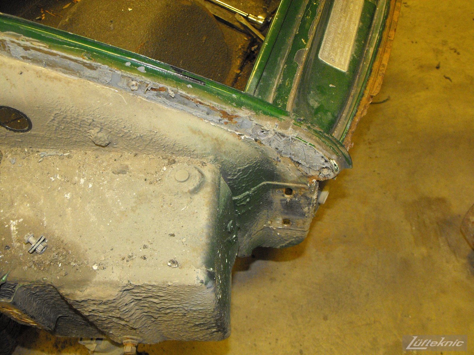 Front chassis wear and some rust on an Irish Green Porsche 912 undergoing restoration at Lufteknic.