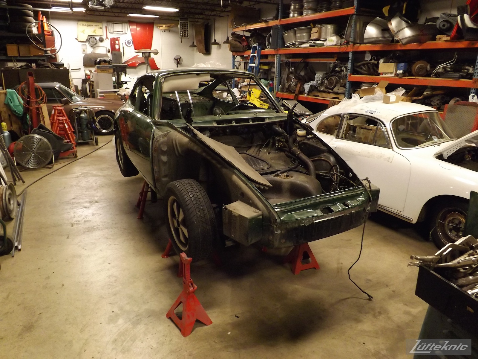 An overall picture of the chassis on jack stands of an Irish Green Porsche 912 undergoing restoration at Lufteknic.