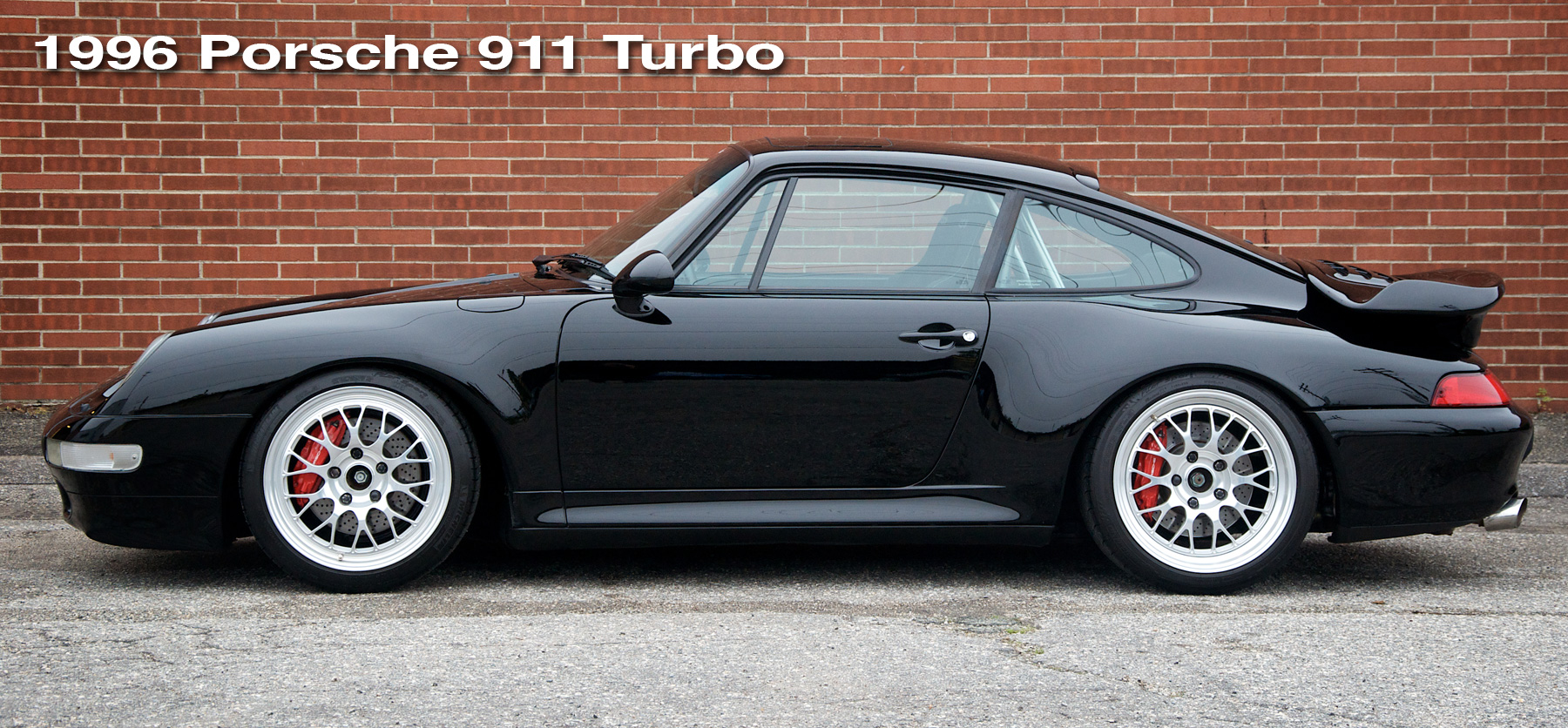 The header image for the 993 Turbo project car page showing a black 1996 911 Turbo in front of a brick wall.