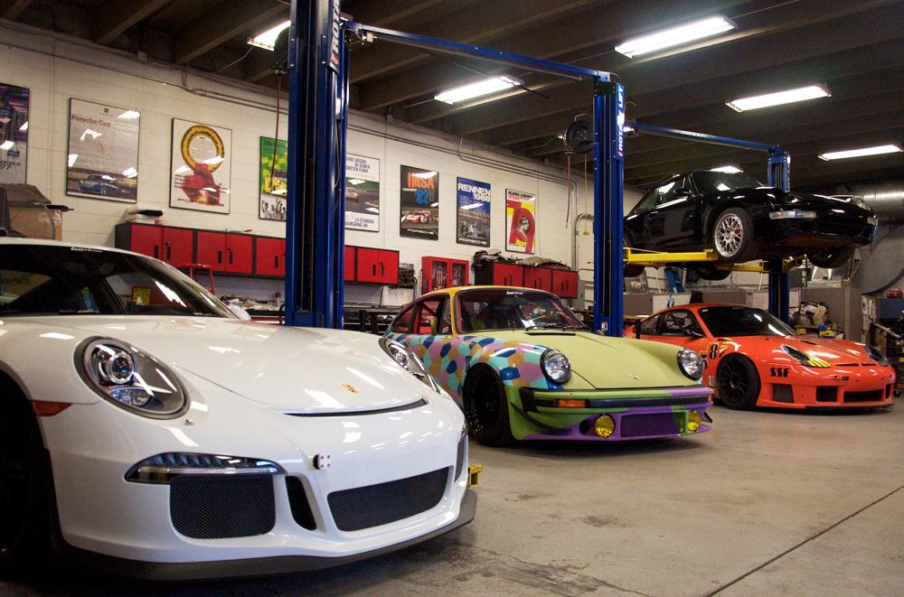 Porsches staged inside the Lüfteknic shop, including 991 GT3, projectstuka, 993 turbo and orange Hazardous Sports 996 GT3 RS