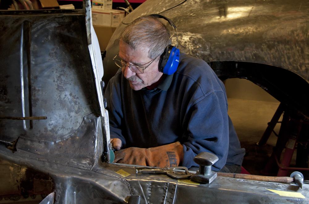A Lüfteknic craftsman grinding on a panel of a Porsche 356 being restored.