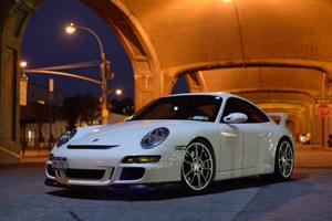 A white 997 GT3 under a bridge at night