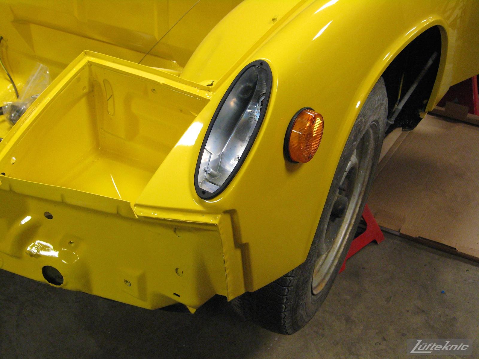 Reassembling a restored yellow Porsche 914 at Lufteknic.